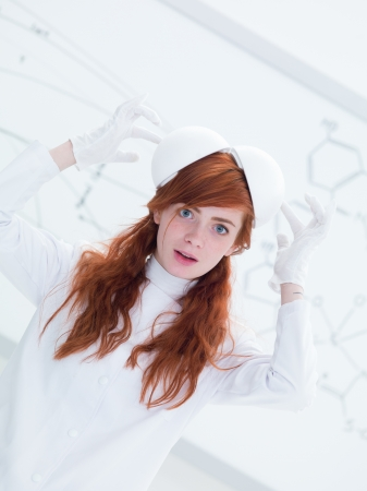 general-view of a pretty face girl student in a chemistry lab playing with lab tools and a  white-board on the background photo
