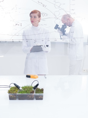 globalwarming: general-view  of a student in a chemistry lab analyzing graphics and her teacher analyzing under microscope in the background of a transparent board around lab table with a box of grass on it