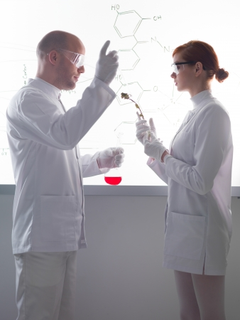 analytical: side-view of two people conducting an experiment with plants and  colorful liquids in a chemistry lab  with a white-board on the background