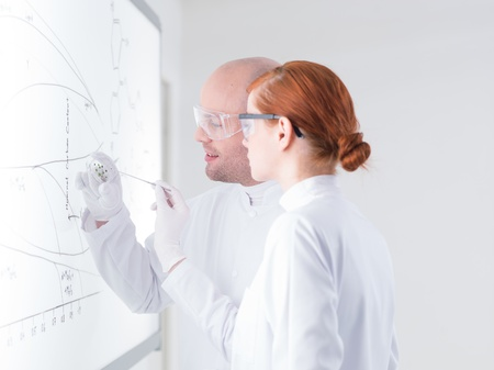 latex: close-up of a teacher in a chemistry lab holding in hand samples for his student in front of a whiteboard