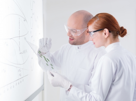 close-up of a teacher in a chemistry lab showing some samples to his student in front of a whiteboard photo