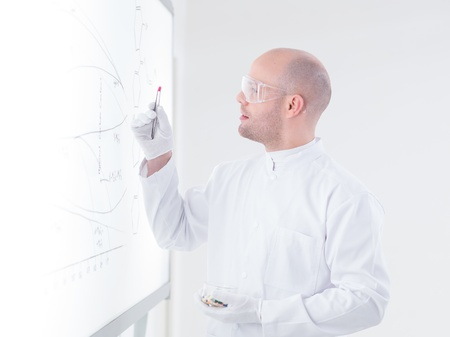 side-view  of a scientist in a chemistry lab holding in his hands and analyzing a pink pill in front of a whiteboard photo