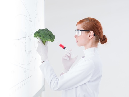 experimentation: side-view  of one beautiful student injecting a broccoli in front of a whiteboard