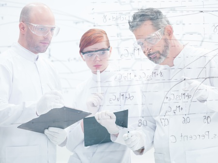 close-up of tree people in a laboratory analyzing data from a whiteboard photo