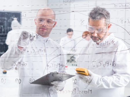 close-up  of two researchers in a lab writing formulas on a transparent board and scanning results with another two student in the background
