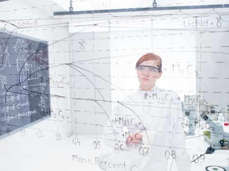 scientist woman: general-view of a student in a chemistry lab analyzing formulas and graphics on a transparent board