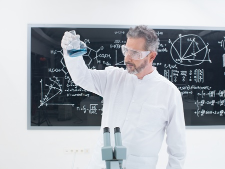 general-view of a scientist in a chemistry lab analyzing colorful substances around laboratory tools and  with a blackboard on the background 版權商用圖片