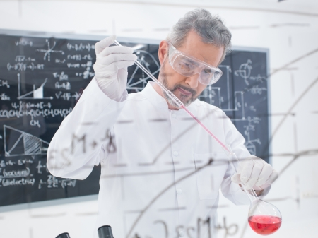 close-up of scientist conducting a chemical laboratory experiment with colorful liquids and a blackboard with formulas on the background photo