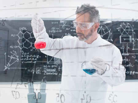 close-up of scientist conducting a chemical laboratory experiment with colorful liquids and a blackboard with formulas on the background 版權商用圖片