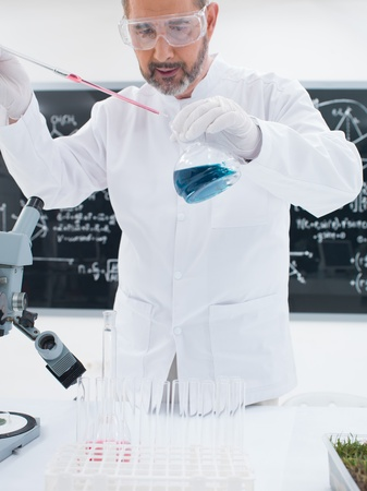close-up of a chemist in a laboratory conducting an experiment with blue liquids around a lab table