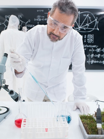 close-up of a scientist in a chemistry lab analyzing colorful liquids on a lab table with another one on the background  writing formulas on a blackboard