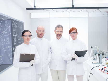 general-view of smiling researchers team in a chemistry lab around lab table with lab tools and colorful liquids photo