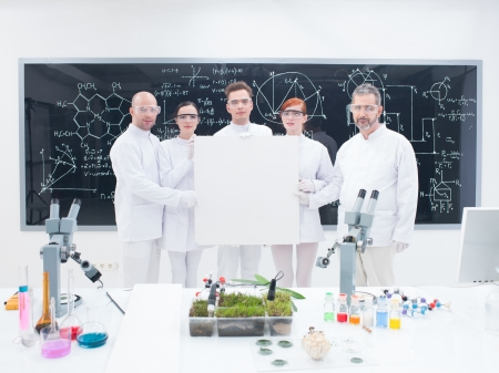 close-up of five scientists in a chemistry lab holding in hands an empty banner and confident looking in the camera with a blackboard on the background photo