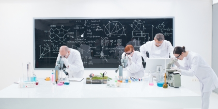 close-up  of researchers in chemistry lab analyzing under microscope on a worktable around lab tools and colorful liquids and a blackboard with formulas on the background