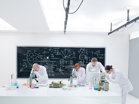worktable: general-view of researchers in chemistry lab analyzing under microscope on a worktable around lab tools and colorful liquids and a blackboard with formulas on the background