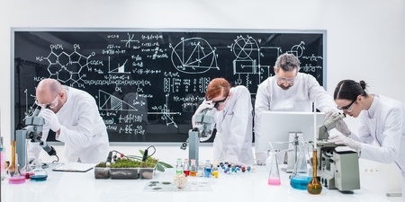 chlorophyll: close-up  of researchers in chemistry lab analyzing under microscope on a worktable around lab tools and colorful liquids and a blackboard with formulas on the background