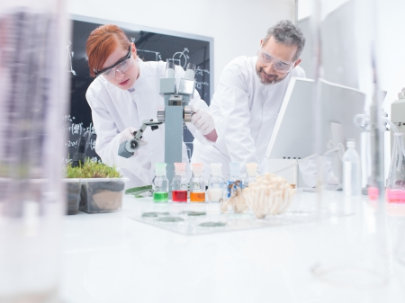 analytical: close-up of a student in a chemistry lab around lab tools and colorful liquids conducting an experiment under microscope under the observation of her teacher
