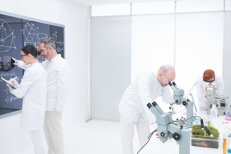 general-view of a teacher in a chemistry lab pointing formulas on a blackboard for his student taking notes while another two scientists analyzing under microscope photo
