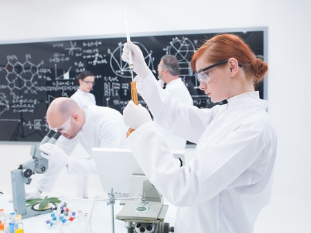 close-up of a student in chemistry lab conducting an experiment with colorful iquids and another three people analyzing data