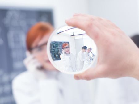 hypothesis: close-up of a beautiful student in a chemistry lab having fun and looking through a magnifier