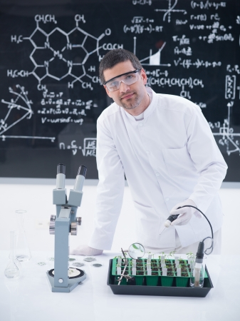 globalwarming: close-up of a scientist in a chemistry lab conducting a seedlings experiment on a lab table with lab tools and a blackboard on the background Stock Photo