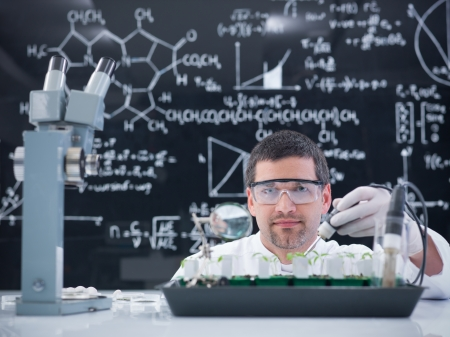 globalwarming: close-up of a man in a chemistry lab conducting a plant experiment on a lab table with lab tools and a blackboard on tha background