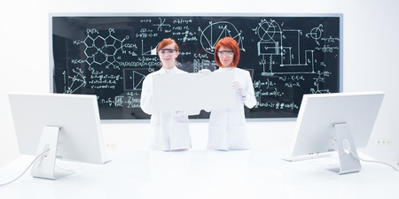 general-view of two students in a chemistry lab around a lab table with two pc monitors on it  holding in hands an empty banner and a blackboard on the background photo