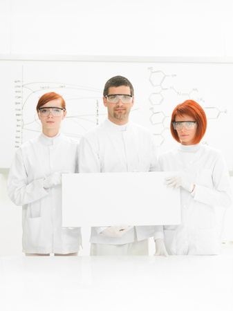 drug discovery: close-up of two beautiful women and a man in a chemistry lab  smiling in the camera with a whiteboard with formulas on the background