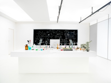 general-view of a chemistry laboratory with a lab table containing colorful liquids and lab tools and a blackboard on the background