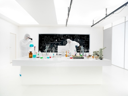 liquids: general-view of two scientists in a chemistry lab conducting an experiment around a lab table with colorful liquids and lab tools with a blackboard on the background Stock Photo