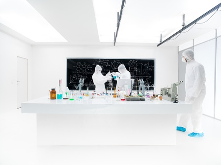 hypothesis: general-view of two scientists in a chemistry lab conducting an experiment around a lab table with colorful liquids, lab tools and magic gas with a blackboard on the background and another one observing the experiment Stock Photo