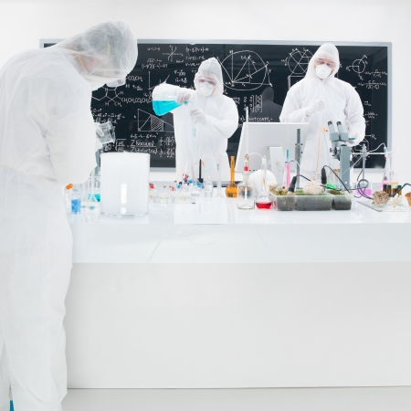 close-up of three scientists in a chemistry lab conducting an experiment around a lab table with colorful liquids and lab tools with a blackboard on the background photo