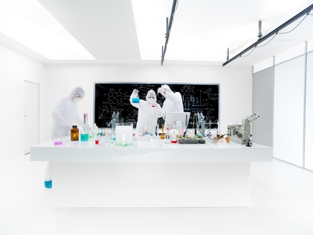 general-view of three scientists in a chemistry lab conducting an experiment around a lab table with colorful liquids and lab tools with a blackboard on the background photo