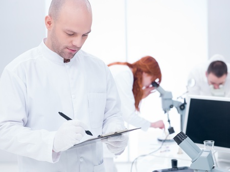 taking notes: close-up of a scientist taking notes in a chemistry lab and another two students analyzing under microscope in the background around a lab table Stock Photo