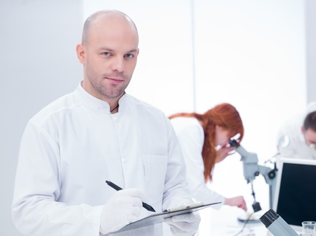 close-up of a smiling scientist holding a clip-board in a chemistry lab around a worktable where two other people analyzing under microscope Stock Photo - 20635618