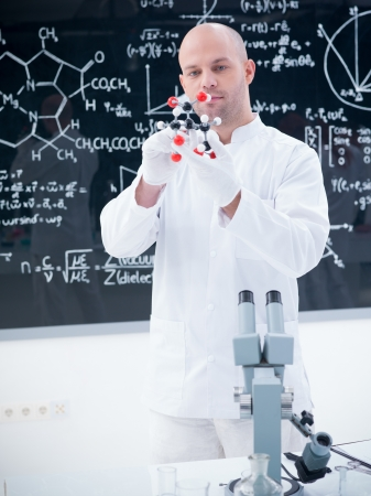 close-up of a scientist analyzing a citric acid molecular model  in a chemistry lab with a blackboard on the background
