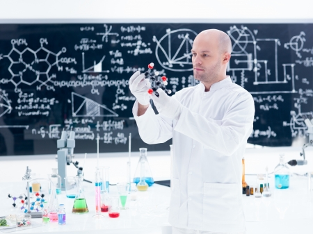 side-view of a scientist analyzing a  citric acid molecular model  in a chemistry lab around a lab table with colorful liquids and lab tools and a blackboard on the background photo