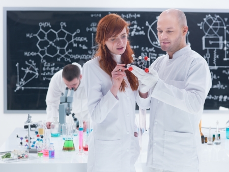 citric: general-view of two people analyzing a  citric acid molecular model  in a chemistry lab around a lab table with colorful liquids and lab tools and another man analyzing under microscope with a blackboard on the background