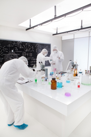 general view  of people working in a chemistry lab around a lab table with colorful liquids and lab tools with a blackboard on the background. photo