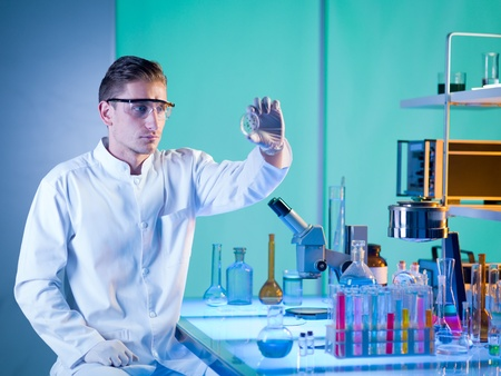 close-up of lab technician holding a petri dish with a sample, analysing it photo