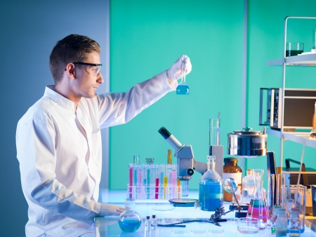 side view of pharmacist in a laboratory holding a chemistry bottle with blue substance in it photo