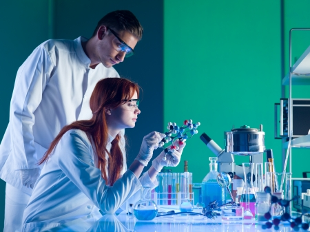 biology lab: side view of two young caucasian scientists studying a molecular structure in a laboratory