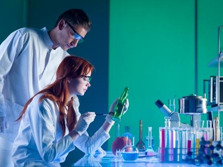 investigacion: vista lateral de dos científicos forenses tomar las impresiones dactilares de la botella, en un laboratorio Foto de archivo