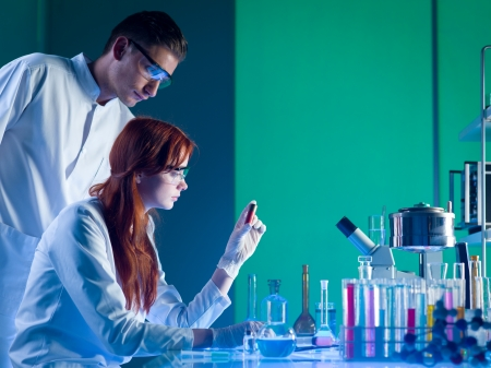 side view of two caucasian forensic scientists looking at a red cartridge with fingerprints on, in a laboratory Stock Photo