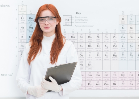 periodic table of the elements: close-up of young beautiful female scientist holding a clipboard in her arms, with periodic table in background