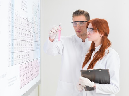 periodic table of the elements: close-up of young caucasian scientists looking at a test-tube filled with pink substance, in front of periodic table, on white background Stock Photo