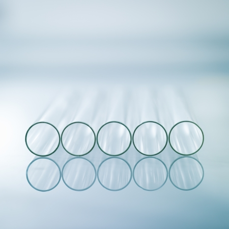 laboratory labware: A close-up of five horizontal medical test tubes on a light blue gradient background