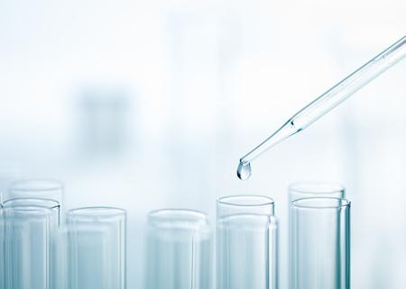 Een close-up van een laboratorium glazen pipet met opkomende druppel stof dan een van meerdere reageerbuizen op een lichte achtergrond