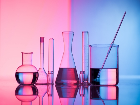 laboratory labware: Different laboratory glassware with water and empty with reflection. Pink and blue tint background Stock Photo