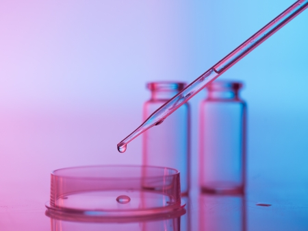 pipette dropping a transparent liquid in an empty petri dish with two empty beakers in the background against a gradient blue and purple background photo